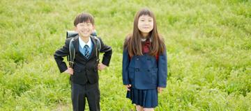 小学生の男の子と女の子が生い茂る黄緑色の草の上に立ってこちらに微笑んでいる写真